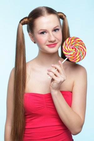 Beautiful playful young freckled girl with lollipop on blue background Stock Photo - 18208681