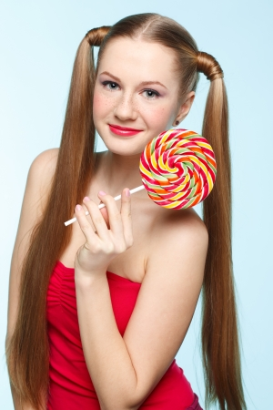 Beautiful playful young freckled girl with lollipop on blue background Stock Photo - 18208664