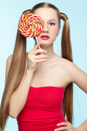 Beautiful playful young freckled girl with lollipop on blue background photo