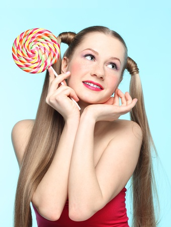Beautiful playful young freckled girl with lollipop on blue background Stock Photo - 18208654