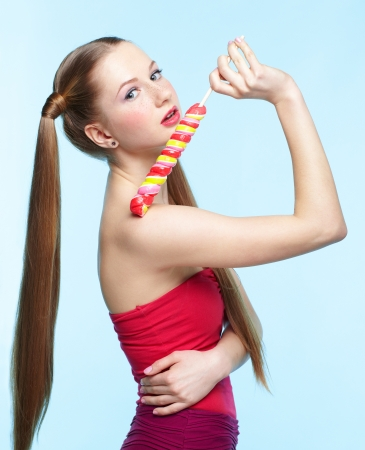 Beautiful playful young freckled girl with lollipop on blue background
