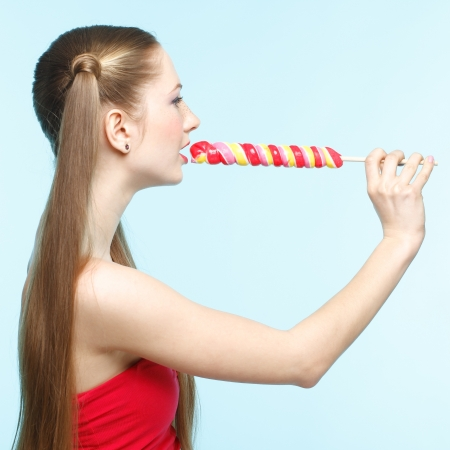 Beautiful playful young freckled girl with lollipop on blue background Stock Photo - 18208627