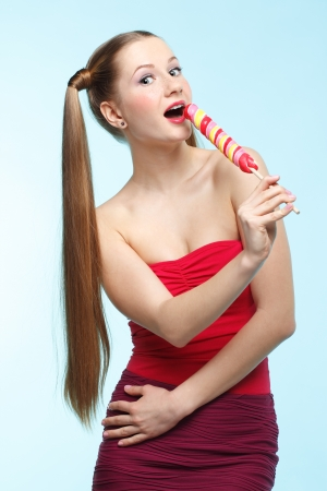 Beautiful playful young freckled singing girl with lollipop on blue background Stock Photo - 18208657