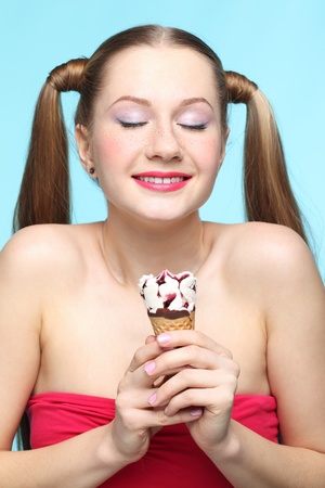 closed eye: Beautiful playful young freckled girl with  ice cream on blue background Stock Photo