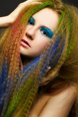 headshot portrait of young beautiful redhead woman with long hair colored with green blue and red photo