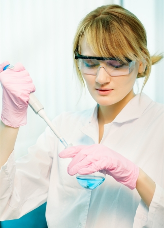 portrait of young woman scientist in lab injecting liquid with pipette into retort photo