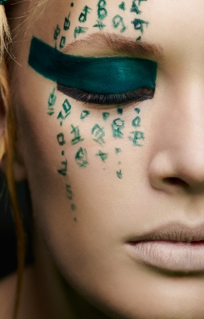 close-up portrait of beautiful young woman with hieroglyphic body art photo