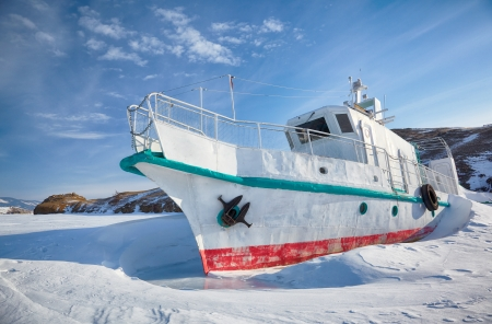 Ship at moorage in frozen baikal lake at winter season photo