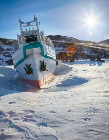 Ship at moorage in frozen baikal lake at winter under Sun rays photo