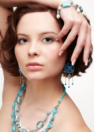 closeup portrait of beautiful brunette young woman in blue beads, ear-rings and bracelet