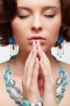 close up portrait of beautiful brunette young woman in blue beads and ear-rings photo