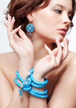 portrait of beautiful brunette young woman with hands tied-up with teal beads