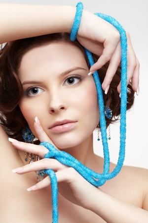 portrait of beautiful brunette young woman with teal beads on gray photo