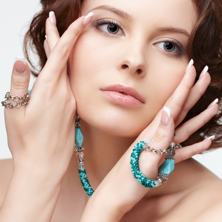 portrait of beautiful brunette young woman with teal beads touching her cheeks photo