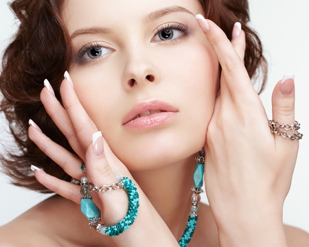portrait of beautiful brunette young woman with teal beads touching cheeks photo