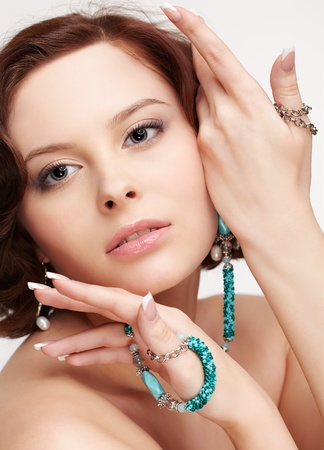 portrait of beautiful brunette young woman with teal beads in manucred hands photo