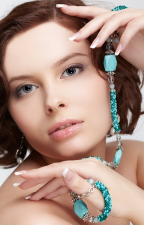 portrait of beautiful brunette young woman with teal beads in hands photo