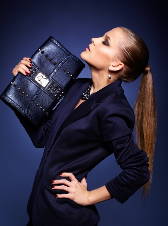 Portrait of beautiful young businesswoman on blue with purse Stock Photo
