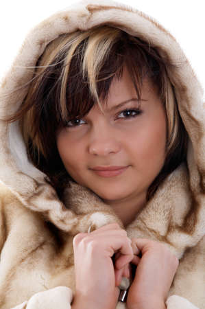 Portrait of smiling girl in fur coat on white background photo