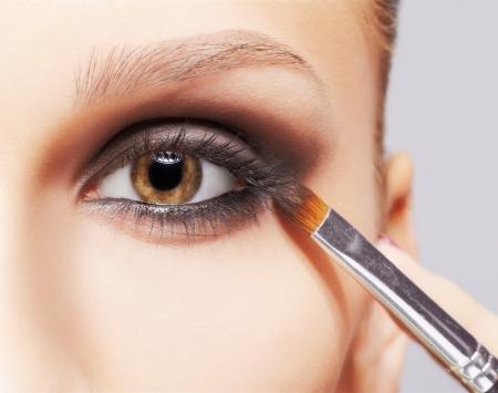 closeup portrait of beautiful young brunette woman applying eye-zone makeup with cosmetic brush Stock Photo