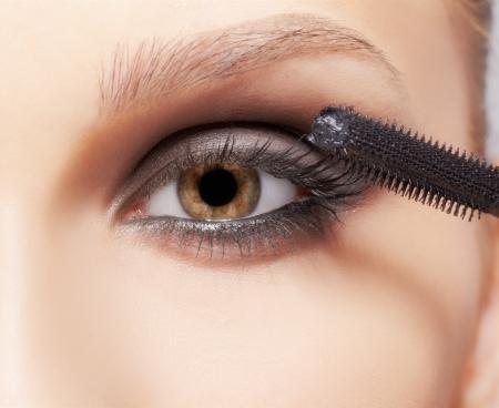 close-up portrait of beautiful young brunette woman applying mascara photo