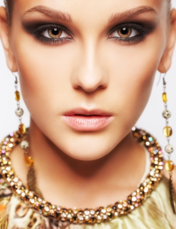 headshot portret van mooie jonge brunette vrouw in het oor-ringen en kraag op grijs Stockfoto