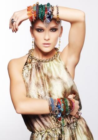 portret van mooie jonge brunette vrouw in het oor-ringen en meerdere armbanden op grijs Stockfoto