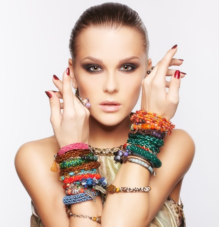 portrait of beautiful young brunette woman posing in multiple bracelets on gray