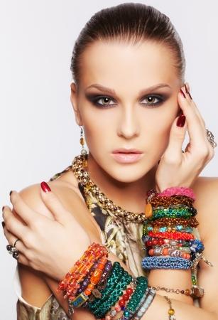 portret van mooie jonge brunette vrouw in de kraag en meerdere armbanden op grijs Stockfoto