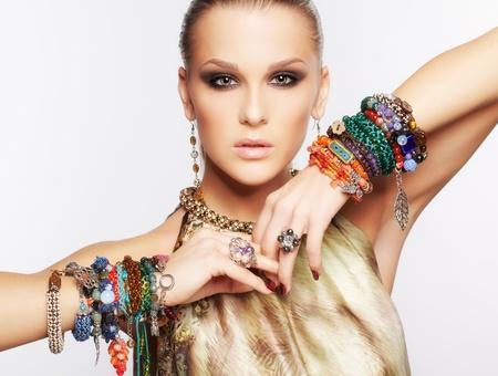 portret van mooie jonge brunette vrouw in meerdere armbanden en andere sieraden op grijs
