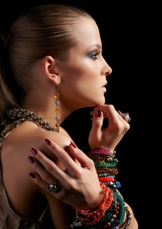 sideview portrait of beautiful young brunette woman in multiple bracelets and other jewelry on dark gray photo