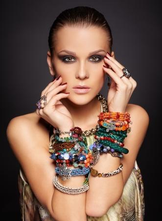 portret van mooie jonge brunette vrouw in meerdere armbanden en ringen op donkergrijs Stockfoto