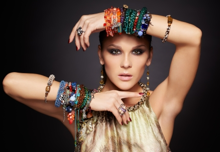 portret van mooie jonge brunette vrouw in meerdere armbanden en oor-ringen op donkergrijs