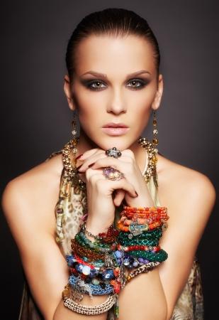 portret van mooie jonge brunette vrouw in ringen en meerdere armbanden op donkergrijs Stockfoto
