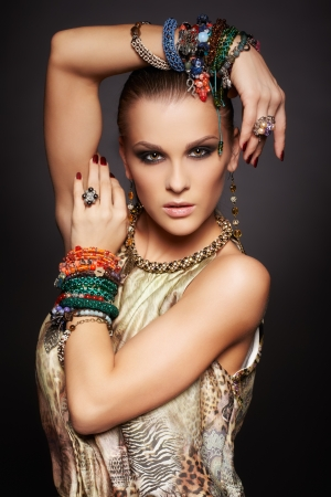 portrait of beautiful young brunette woman posing in rings, collar, ear-rings and multiple bracelets
