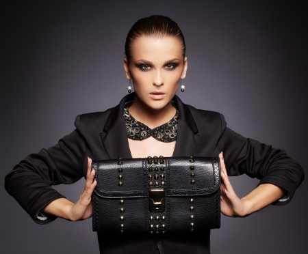 portrait of beautiful young brunette woman in jacket with black leather clutch on dark gray