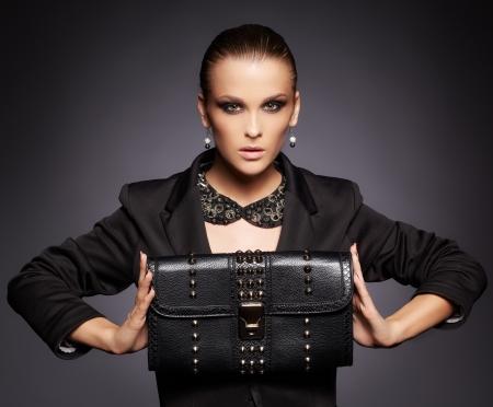 portret van mooie jonge brunette vrouw in jas met zwarte lederen clutch op donkergrijs
