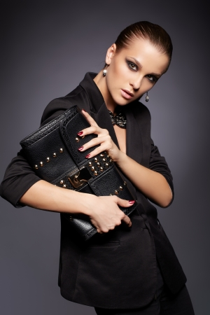 portrait of beautiful young brunette woman in stylish black jacket with leather clutch on dark gray photo