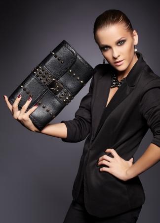 portret van mooie jonge brunette vrouw in een stijlvolle zwarte jas met lederen clutch op grijs