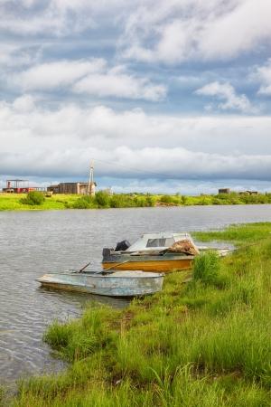 carex: Boats  on the river near settlement Pokhodsk on Kolyma in Sakha Yakutia Stock Photo