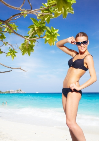Young beautiful woman in bikini on the beach under tree of Messerschmidia argentea photo