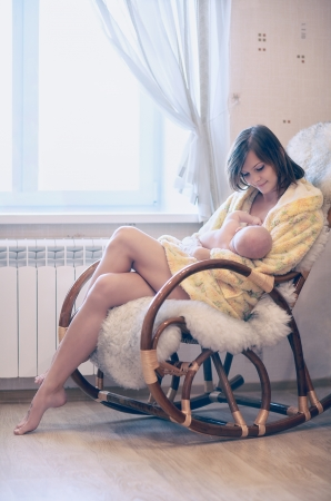 Young mother feeding baby in nursery bedroom Stock Photo - 21893753