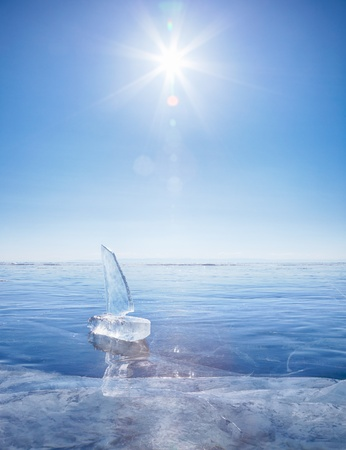 太陽光の下で冬バイカル湖に氷のブロックから成っているヨット