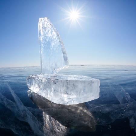 Yacht made of ice blocks on winter lake Baikal under Sun rays photo