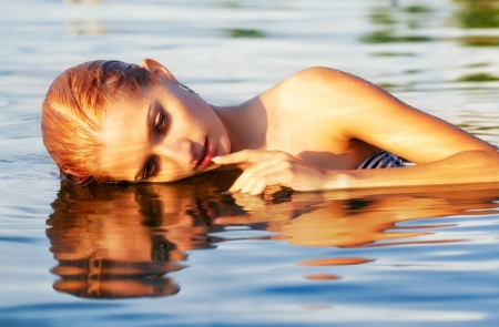 portrait of young beautiful blonde woman in sea waters touching her lips photo
