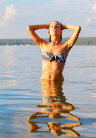 portrait of young beautiful blonde woman posing in sea waters photo