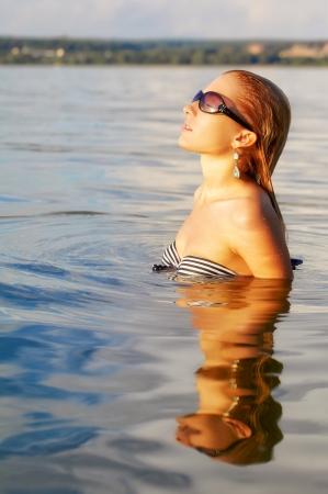 blonde bikini: outdoor portrait of young beautiful tanned blonde woman posing in ocean waters Stock Photo