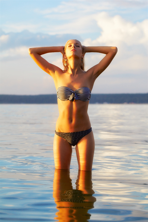 full-length portrait of young beautiful tanned blonde woman posing in sea waters photo