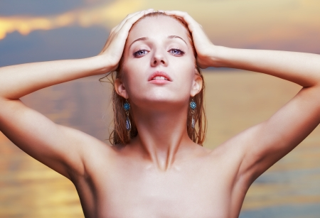armpit hair: portrait of young beautiful blonde woman in blue ear-rings  ocean on background