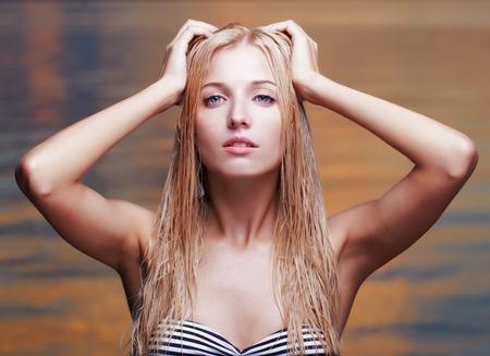 wet bikini: portrait of young beautiful blonde woman in bikini with wet hair  sea waters on background